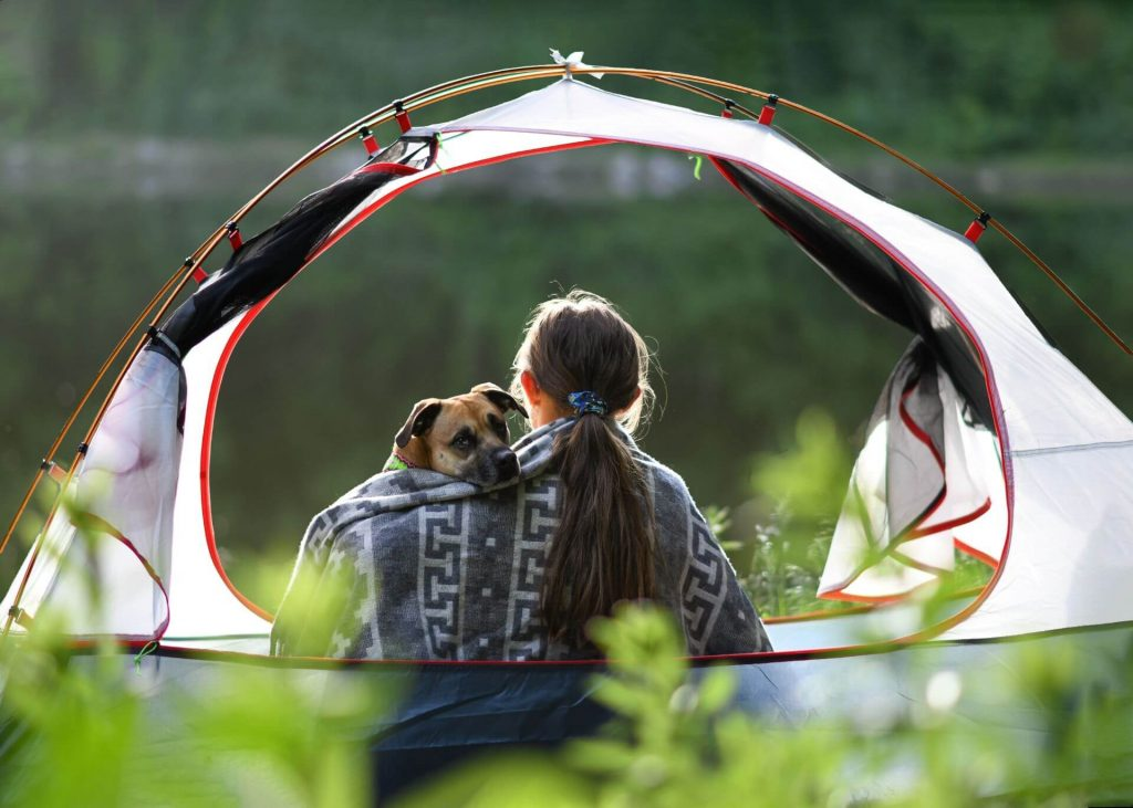 girl and dog wrapped up sharing a cozy blanket in a tent